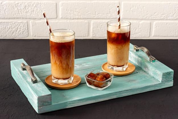 Café glacé sur un plateau en bois avec de la crème qui y est versée, montrant la texture et l'aspect rafraîchissant de la boisson.