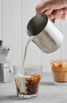 Café glacé sur une table en béton gris, versant la crème, mettant en valeur la texture et l'aspect rafraîchissant de la boisson