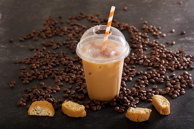 Café glacé en verre en plastique avec des haricots sur table sombre