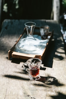 Café goutte à goutte chaud en verre à boire sur la table en bois avec la lumière du soleil dure.