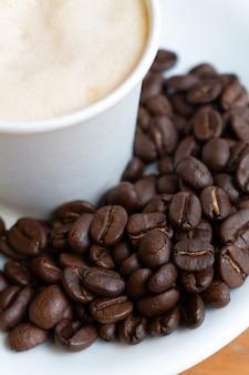 Café de graines crues sur le plat blanc et café blanc flou de tasse blanche floue,