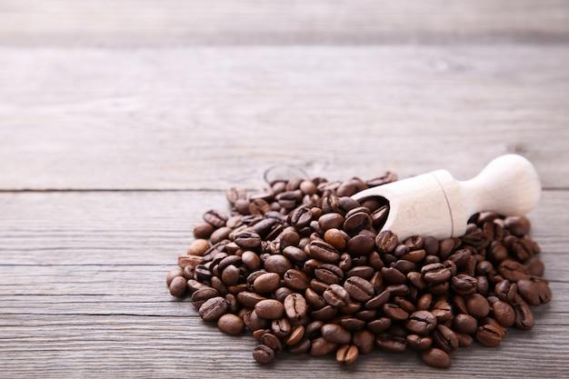 Café en grains dans une cuillère en bois sur fond gris.