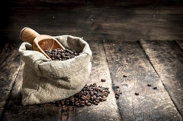 Café en grains dans un sac. sur un fond en bois.
