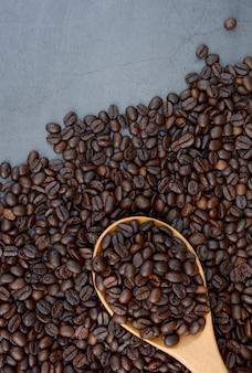 Café en grains avec fond de cuillère à café avec espace.