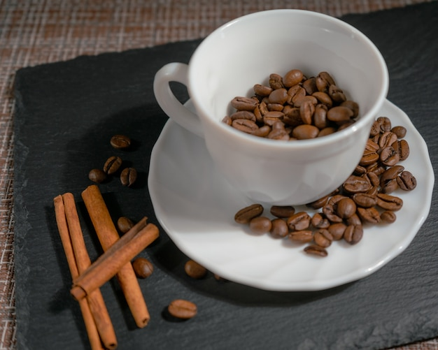 Café en grains torréfiés, avec des bâtons de cannelle dans une tasse en céramique blanche, sur une surface brune, close-up