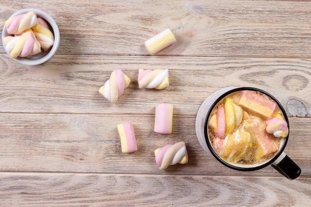 Café avec des guimauves sur une table en bois blanc