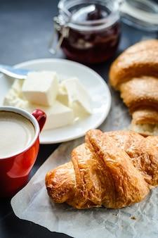 Café avec de l'huile de croissants et de la confiture sur la table.