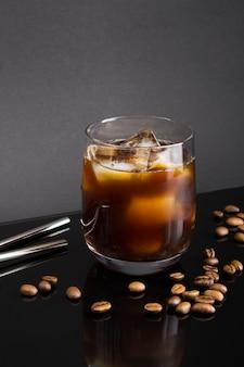 Café infusé à froid dans le verre à boire sur fond noir. emplacement vertical.