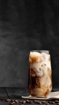 Le café et le lait sont mélangés dans un verre highball avec de la glace. table en bois gris.