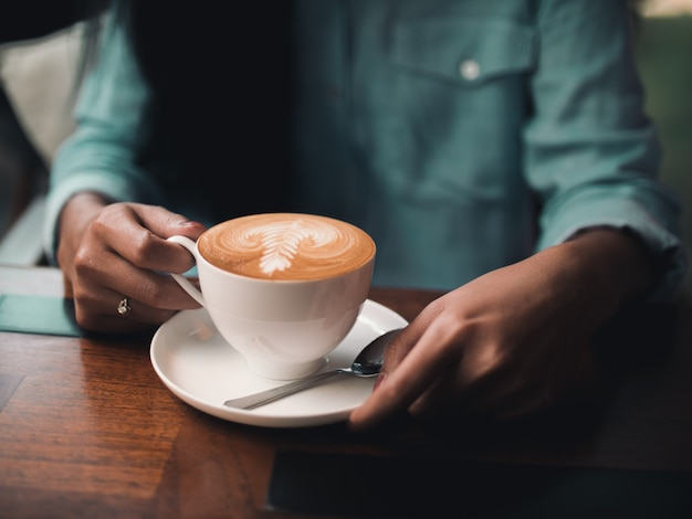Café latte art au café avec une main de femme