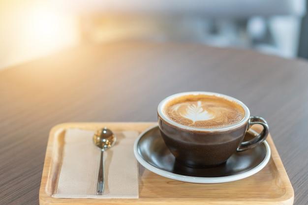 Café latte d'art chaud dans une tasse sur la table en bois dans le café-restaurant flou fond