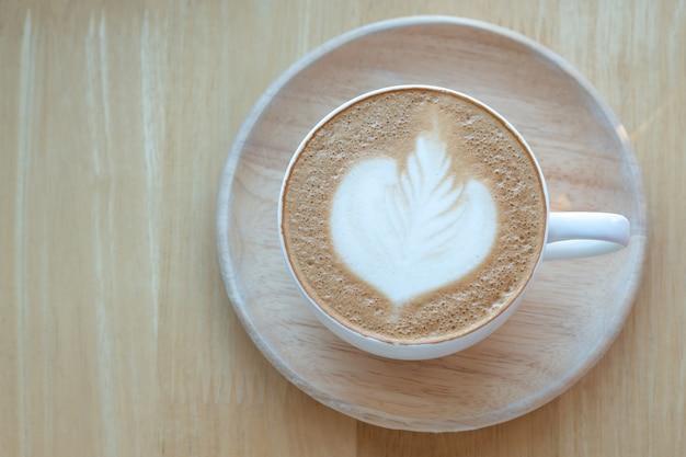 Café latte art et grains de café torréfiés au matin avec le soleil sur