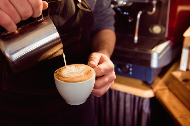 Café latte barista faire motif dans une tasse de café.
