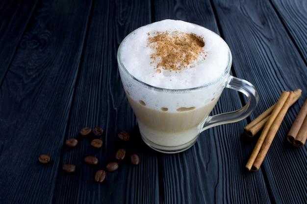 Café latte à la cannelle dans la tasse en verre sur le bois noir