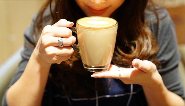 Café latte chaud dans la main de la fille asiatique, poste et prêt à boire.
