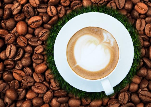 Café latte chaud dans une tasse blanche sur les grains de café
