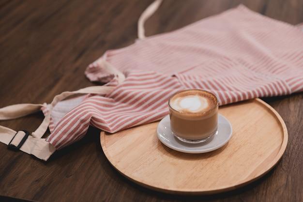 Café latte chaud pour servir avec tablier sur table dans le café.