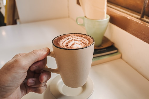 Café latte chaud servi dans une tasse blanche sur la table le matin