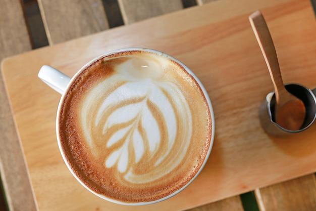 Café latte chaud vue de dessus avec motif coeurs et sirop sur table en bois