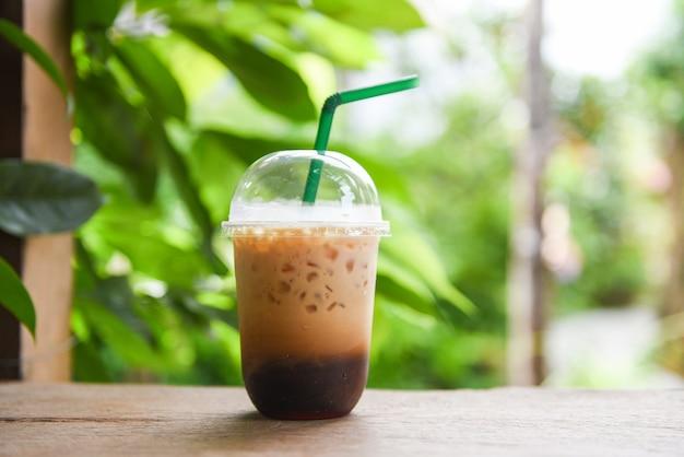 Café latte glacé dans une tasse en plastique sur une table en bois et fond vert nature