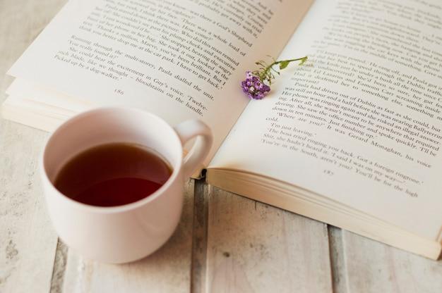 Café et livre ouvert avec des fleurs à l'intérieur