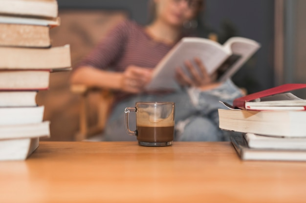Café et livres près de la lecture de femme