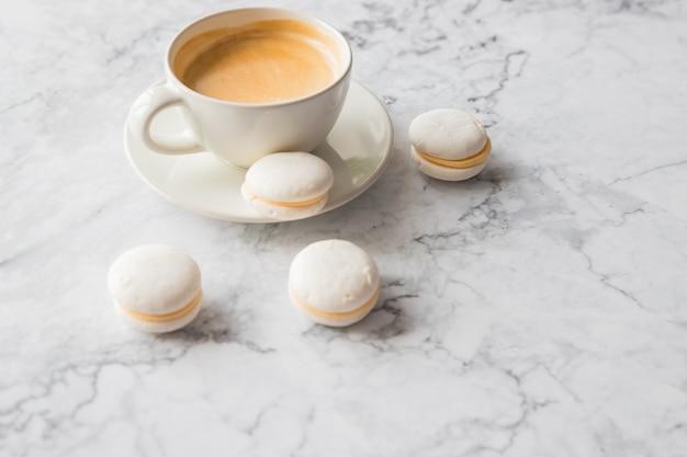 Café et macarons français sur fond de marbre.