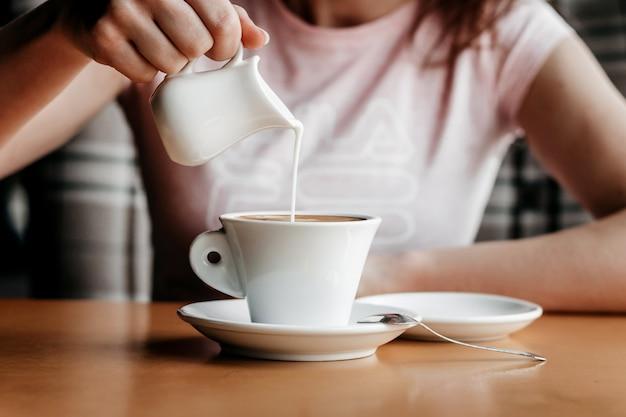 Café matinal. gros plan des mains de femmes avec une tasse de café dans un café. mains féminines tenant des tasses de café sur une table en bois dans un café, ton de couleur vintage