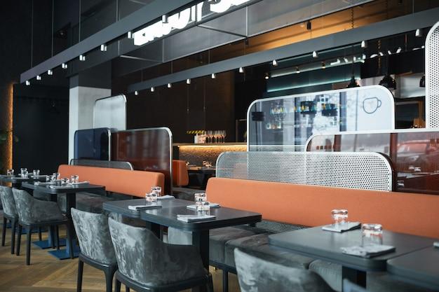 Café à la mode avec des meubles gris et des panneaux de formes différentes entre les zones, des planches en bois avec des lampes au-dessus des tables