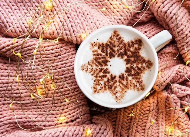Café avec un motif de flocon de neige sur une surface de chandail tricotée chaude