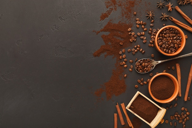 Café moulu assorti et grains torréfiés dans des bols et dispersés sur une ardoise texturée grise, vue de dessus, espace de copie. conception de modèle pour la publicité d'un café ou d'un café