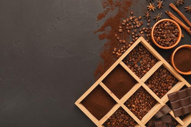Café moulu assorti et grains torréfiés dans un cadre carré en bois et des bols sur ardoise texturée grise, vue de dessus, espace de copie. conception de modèle pour la publicité d'un café ou d'un café