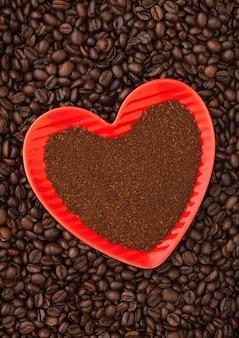 Café moulu dans une assiette en forme de coeur rouge sur fond de grains de café frais. vue de dessus