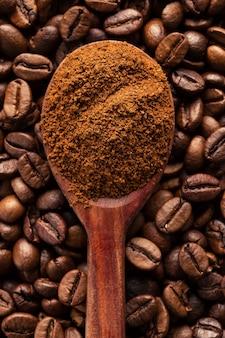 Café moulu dans une cuillère vintage sur des grains de café.