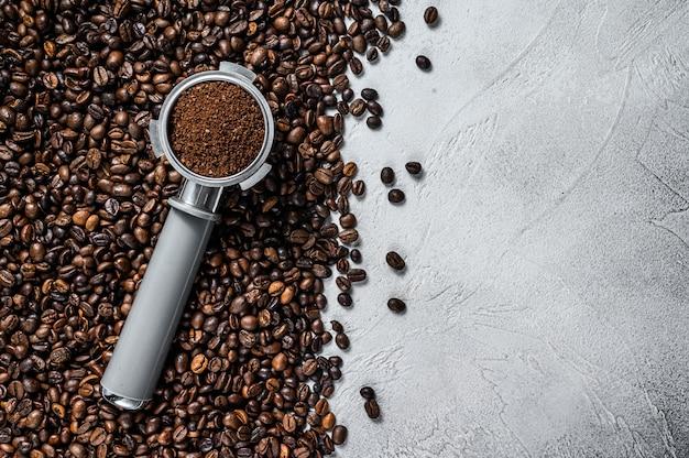 Café moulu dans le porte-filtre pour espresso avec des grains de café sur blanc. vue de dessus.