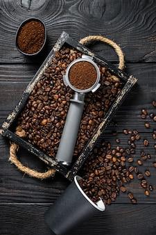 Café moulu dans un porte-filtre pour expresso dans un plateau en bois avec des grains de café.