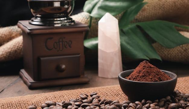 Café moulu en grains de café torréfié en pierre de quartz grinderrose et monstera partent sur table en bois avec surface en toile