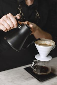 Café moulu noir. barista prépare un verre. café dans une cruche en verre.