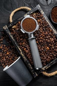 Café moulu en porte-filtre pour espresso dans un plateau en bois avec table en bois de grains de café. vue de dessus.