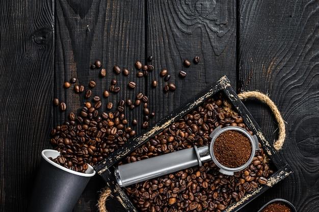 Café moulu en porte-filtre pour expresso dans un plateau en bois avec des grains de café