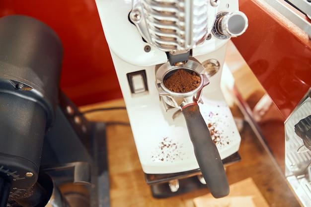 Café moulu versé dans un porte-filtre avec un moulin.