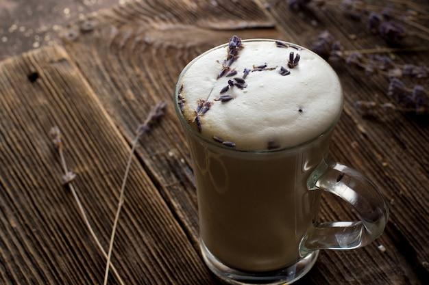 Café avec de la mousse de lait dans une tasse transparente avec des brindilles de lavande.