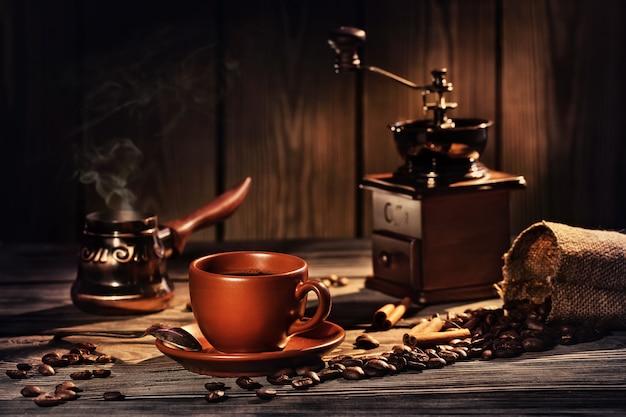 Café nature morte avec une tasse, un moulin à café et des grains