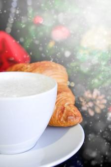 Café de noël coupe en verre blanc cappuccino chaud avec des croissants et décoration de noël