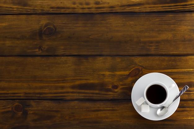 Café noir à 2 sucres, tasse blanche sur une table en bois marron. vue de dessus