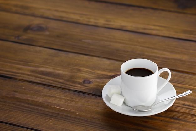 Café noir à 2 sucres, tasse blanche sur une table en bois marron.