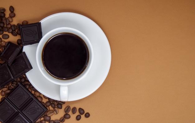 Café noir américain sans lait dans une tasse blanche, chocolat et grains de café. vue de dessus, mise à plat, place pour le texte. une tasse de café du matin aromatique. joli fond pour café, menu de restaurant.
