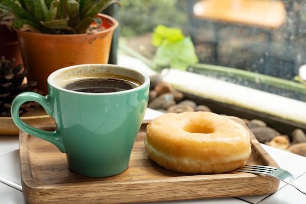 Café noir americano et beignet dans un plateau en bois