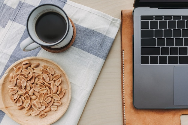 Café noir aux cacahuètes salées et ordinateur portable sur le bureau