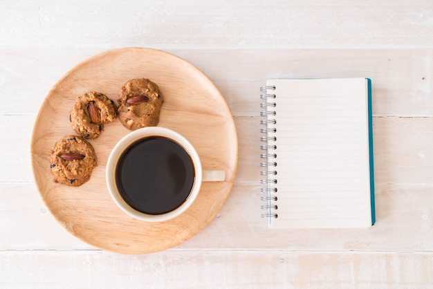 Café noir et biscuits avec ordinateur portable et cahier